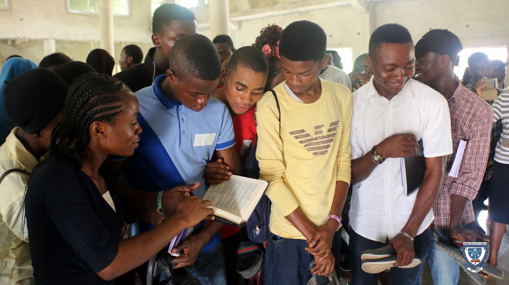 A group of fresh students flipping through the pages of the Holy Quran during a tour to the University Central Mosque to demonstrate brotherliness among the two religious bodies on campus as part of the orientation exercise