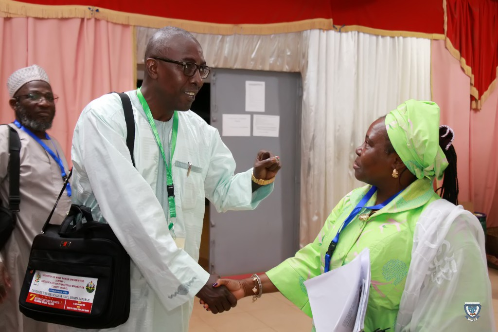 The Vice-Chancellor, Prof. Angela F. Miri in a warm handshake with one of the participants at the 7th Conference and 9th AGM of the Association of West Africa Universities held in Benin Republic