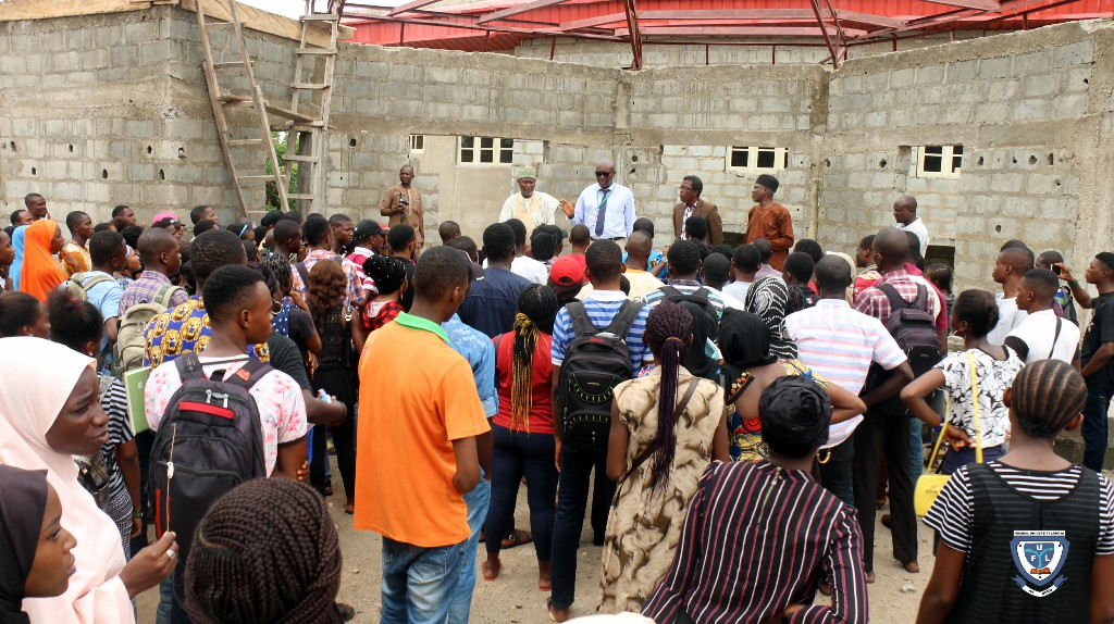 Fresh students and the two religious leaders at the Chapel of Grace church building which is still under construction